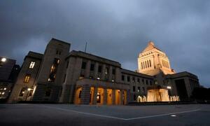 夕暮れに浮かび上がる国会議事堂。岸田首相は14日、衆院を解散する=13日