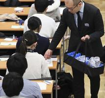 大学入試センター試験の1日目で、受験生に英語のリスニング用のICプレーヤーを配布する担当者=1月18日午後、東京都文京区の東京大学(代表撮影)