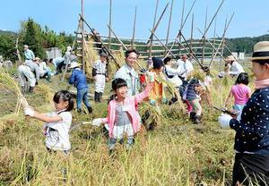 黄金色に実った稲穂を刈り取り、笑顔を見せる参加者=24日、福井県越前市