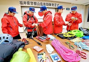 発足式の後、配備された装備品を点検する山岳救助隊員=11日、福井県警本部