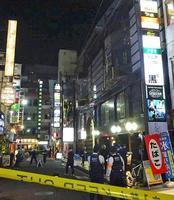 女性がビルから転落し、通行人にぶつかった現場付近を調べる捜査員=2日午後8時26分、東京都新宿区歌舞伎町