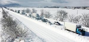 大雪の影響により、北陸自動車道下り線で立ち往生する車の列=1月10日午前10時35分ごろ、福井県福井市寮町から日本空撮・小型無人機ドローンで撮影