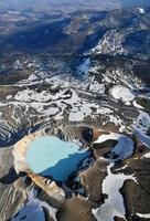 噴火警戒レベルが2に引き上げられた草津白根山の白根山。手前が湯釜=22日午後(共同通信社ヘリから)