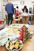 手作りクッキーなどを並べ、クリスマスパーティーの準備をする若者たち。ここには不登校の子どもたちもやって来る=2017年12月、福井県越前市