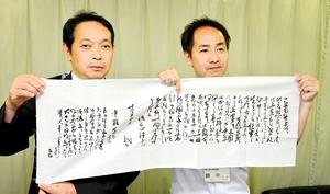 北陸初公開となる龍馬の書状の文章を転写した手ぬぐいと福井市立郷土歴史博物館の角鹿尚計館長(左)ら=8日、福井市役所
