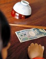 机に置かれた千円札や500円玉が夕食代わりだった(写真はイメージ)