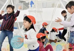 繭型ネット遊具の中でボール投げを楽しむ園児たち=22日、福井県敦賀市神楽町2丁目のキッズパークつるが