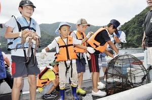 かごからタコを取り出し、手づかみにして歓声を上げる子どもたち=27日、福井県小浜市の海上