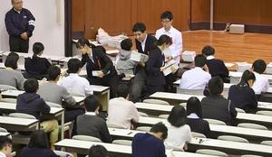 大学入学共通テストの本番を想定したリハーサルで、生徒に問題を配る大学関係者=11月10日午前、東京都目黒区の東大駒場キャンパス