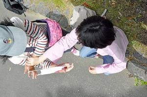 母親の祐子さんがマスクを着けてあげようとすると、嫌がる娘の真衣さん(右)=京都市左京区