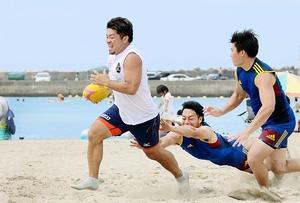 両手でのタッチでタックル成立とみなすビーチラグビー=高浜町の若狭和田海水浴場