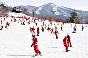 サンタクロース姿で滑りを楽しむ来場者=24日、福井県勝山市のスキージャム勝山