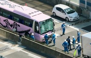 名神高速道路の多重事故現場で、高速バスを調べる警察官=26日午後0時20分、大津市(共同通信社ヘリから)