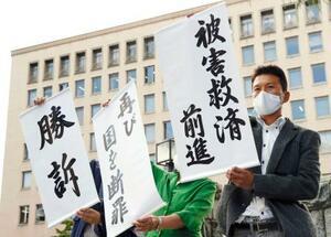 東京電力福島第1原発事故の集団訴訟の控訴審判決後、「勝訴」などと書かれた垂れ幕を掲げる原告の男性(右)ら=30日午後、仙台高裁前