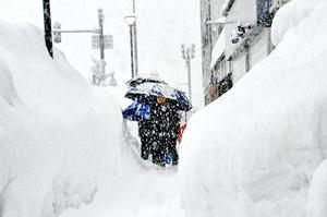 巨大な雪壁の間を下校する子どもたち=6日午後3時15分ごろ、福井県大野市元町