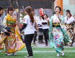 岩手県釜石市でラグビーを体験する晴れ着姿の新成人=13日午後