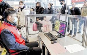 中国湖北省武漢市の鉄道駅で行われている利用客の体温検査=1月21日