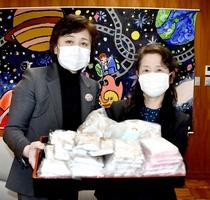 全校児童分の手作りマスクを贈呈した齋藤留美さん(左)と熊田富士子さん=4月8日、福井県鯖江市の進徳小学校
