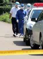 死亡した大里功さんの自宅近くで捜査する茨城県警の捜査員=24日午後、茨城県八千代町