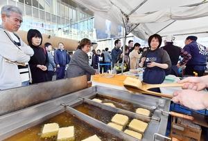 来場者が見守る中、次々と揚げられていく油揚げ=11月23日、福井県福井市のハピテラス