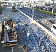 道路上に散らばり撤去される鋼材。奥に止まっているトレーラーが荷崩れを起こした車両=17日午前8時、神戸市