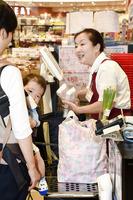 レジ袋を有料化しているスーパーでは、持参したマイバッグに商品を入れてもらう客が多く見られた=6月、福井県福井市のハニークランデール二の宮店