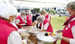 防災訓練で炊き出しをする赤十字奉仕団員。かっぽう着でなく赤いベスト姿で活動した=2017年8月、福井県大野市