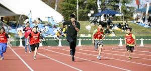 児童と50メートル走で勝負する桐生祥秀選手=11月10日、福井県福井市の9.98スタジアム
