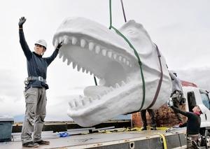 ホワイトザウルスの頭部をクレーンでつり上げる作業員=20日、福井県勝山市