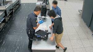 オーストラリア・パース国際空港で携帯電話を調べられる日本人の男(右手前)=2019年11月(オーストラリア国境警備隊提供・共同)
