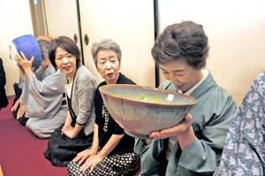 特大の茶わんで薄茶を楽しむ参加者=11日、福井県鯖江市横越町の本山證誠寺