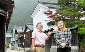 古民家が連なる越前和紙の産地で外国人女性を案内する畑勝浩さん(左)=福井県越前市
