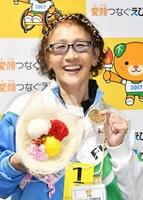 陸上女子ジャベリックスロー2部で優勝し、笑顔で金メダルを手にする上西桃代=松山市の愛媛県総合運動公園陸上競技場