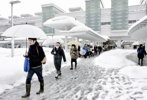 足早に仕事場へ向かう通勤者ら=13日午前8時ごろ、JR福井駅