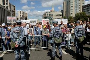 16日、モスクワ中心部で、多数の警察官が警備する中、言論の自由を求め集会に参加した市民ら(共同)
