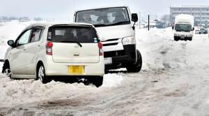 圧雪が緩んで悪路になり、立ち往生が多発した福井市内の道路=10日午前10時50分ごろ、同市新保町