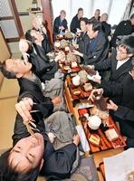 山のように盛られたゴボウを頬張る男衆=17日、福井県越前市国中町