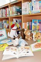 ぬいぐるみが「絵本を選んでいる」シーンなどを写真に収め、貸し出す本とともに子どもに渡す=福井市桜木図書館