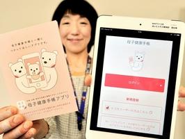 小浜市が導入した「母子健康手帳アプリ」の画面(右)と説明パンフレット=2日、福井県小浜市健康管理センター