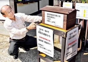 設置した募金箱と「同じ名前だけに支援したい」と話す岸田清会長=6日、福井市の一乗谷朝倉氏遺跡