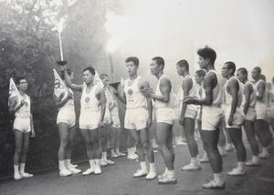 勝見誓司さん(左から3人目)に聖火を引き継ぐ松岡喜一さん(同4人目)=1964年9月28日、福井県若狭町(松岡さん提供)