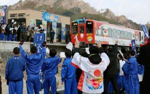 鵜住居駅で釜石東中の生徒らに迎えられる三陸鉄道リアス線のラッピング列車。待合室外壁の絵も生徒らが描いた=24日午前、岩手県釜石市