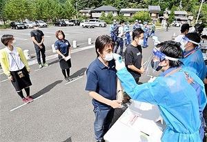 一定の距離を保って検温を受ける訓練の参加者たち=8月27日、福井県おおい町大島のはまかぜ交流センター