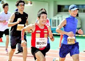 一般ランナーに囲まれながら力走する猫ひろしさん=1日、福井県営陸上競技場