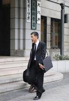 スポーツ現場での暴力根絶に向けた要請書を提出するため、文科省に入る新谷聡さん=19日午後、東京・霞が関