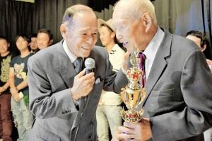 シルバー青空賞を提供し、のど自慢のお年寄りを応援する青空日出夫さん(手前左)と受賞者の藤本誠さん(同右)=18日、福井市のリライム