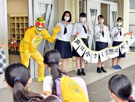 小学校であいさつ運動を行うはっぴーすマン=7月、福井県坂井市内