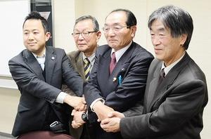 横山龍寛氏への候補者一本化で合意し、握手する福井県内野党・政治団体の代表者=14日夜、福井県教育センター