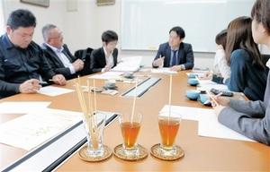 福井県産大麦の茎を使ったストローの商品化に向け、打ち合わせする3社の担当者=福井県福井市今市町のタナックス