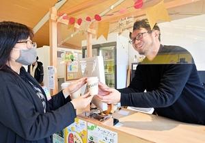 店内で開かれた飲食イベントに訪れた客に笑顔で接する高野哲矢さん(右)=福井県小浜市白鬚のセレクトショップ「TEtoKI」